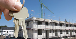 Person's hand holding key infront of a building in construction